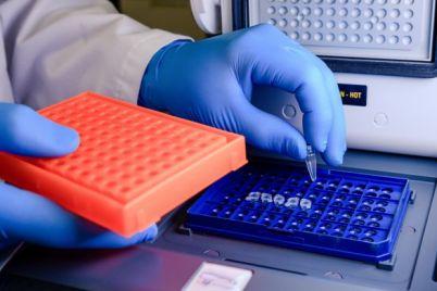 laboratory-worker-arranging-pipette-tips-blue-container-coronavirus-testing_181624-927.jpg